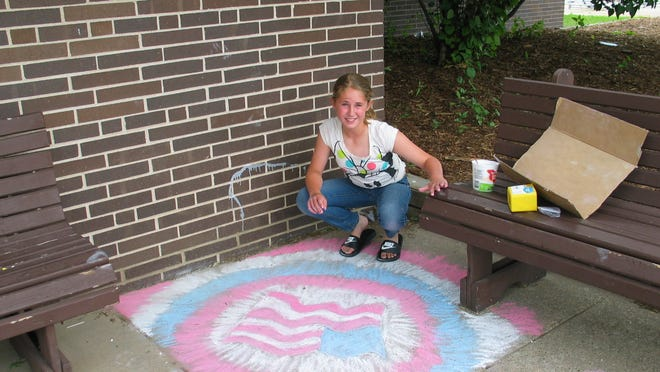 Cassie Schultz uses a Fourth of July-theme for her chalk creation Tuesday during Chalkfest at Ben Franklin Junior High School.