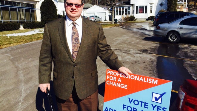 Wausau City Council member Keene Winters stands on March 10, 2015 with a sign encouraging voters to call for a city administrator in an April 7 referendum question on the future of city leadership.