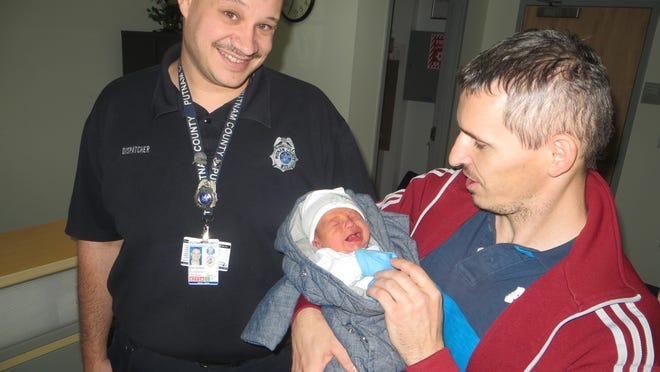 Ladislav Budai of Southeast holds his newborn son, Matej. When Budai's partner, Mariana Hardonova, went into labor Friday, Budai called 911 and dispatcher Brian Burdick, left, talked him through the delivery.