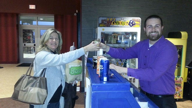 Bear resident Denise Quickle (left) bought the first alcoholic beverage sold Friday at Westown Movies in Middletown from Scott Waugh, the theater's marketing and advertising manager.