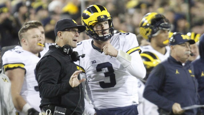Michigan Wolverines coach Jim Harbaugh talks with quarterback Wilton Speight in the first quarter against the Iowa Hawkeyes on Nov. 12, 2016 at Kinnick Stadium in Iowa City.