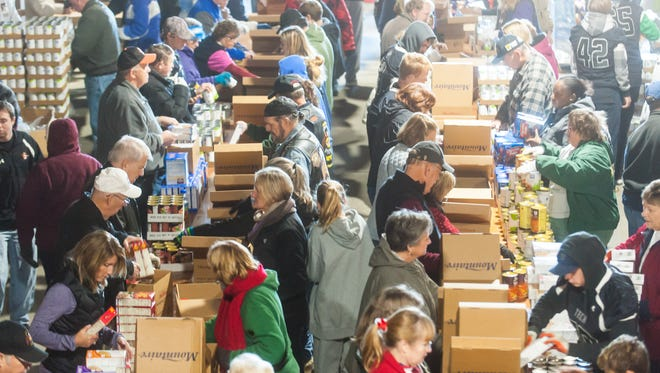 In this 2015 file photo, members of the community help pack Thanksgiving boxes at Mountaire Farms in Selbyville. On Monday, more than 200 volunteers helped package 8,500 meals for families across Delmarva.