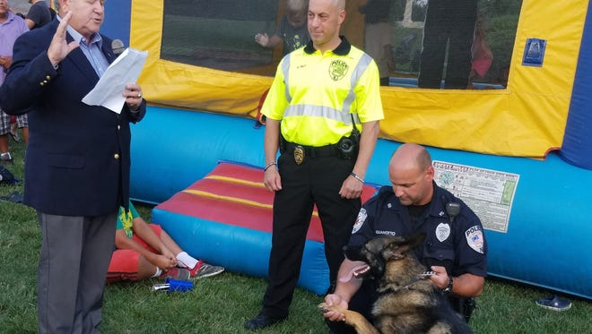 Bound Brook Mayor Robert Fazen swears in K-9 Crusader as an officer in the Bound Brook Police Department at Tuesday's National Night Out. Holding Crusader's paw is his handler, Patrolman Jason Gianotto, and looking on is Chief Vito Bet.
