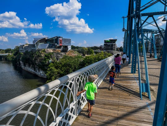 Families walk across the Walnut Street pedestrian bridge