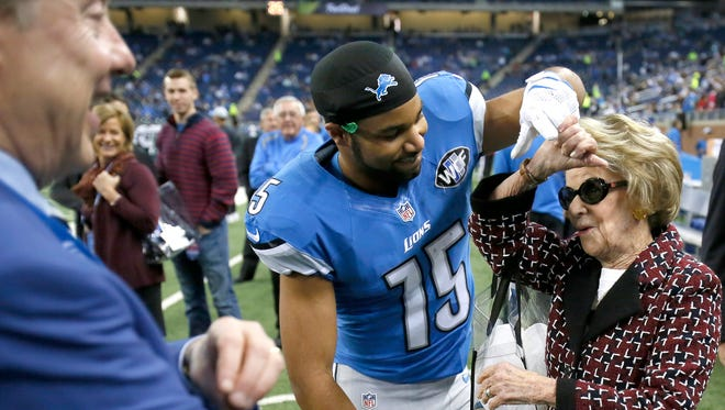 Detroit Lions Vice Chairman Bill Clay Ford Jr., left, watches as Golden Tate, who came over to give a Happy Thanksgiving greeting, takes the hand of team Owner and Chairman Martha Firestone Ford and twirled here in a dance move on the sidelines before the Lions' football game against the Philadelphia Eagles on Thursday, November 26, 2015, in Detroit.