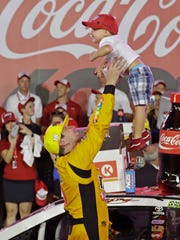 Kyle Busch tosses his son Brexton in the air as he