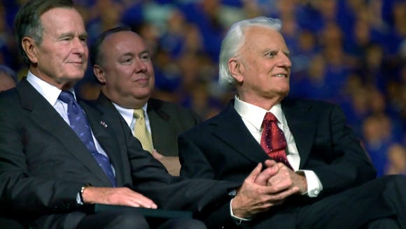 The Rev. Billy Graham, right, grasps the hand of former