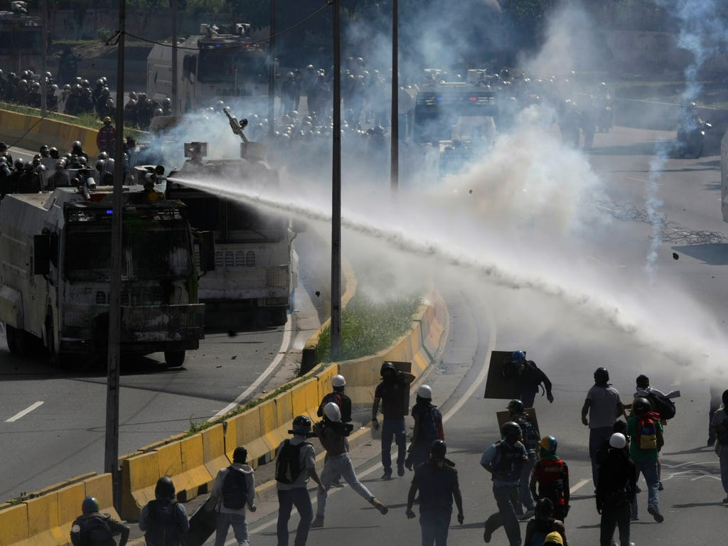 A water canon sprays government protesters trying to reach the Interior Ministry, in Caracas, Venezuela on May 18, 2017. The protest in Caracas comes after a tumultuous 24 hours of looting and protests in the western state of Tachira that led the gov