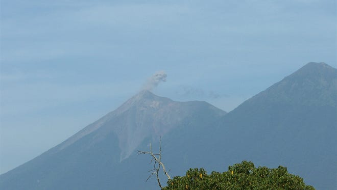 Gray smoke is seen from Fuego, from near Antigua, Guatemala, in 2015. Three volcanoes in this area include Fuego, which erupted this week. At the right is Acatenango, which is dormant.