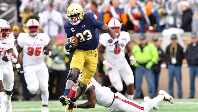 Oct 28, 2017; South Bend, IN, USA; Notre Dame Fighting Irish running back Josh Adams (33) runs the ball as North Carolina State Wolfpack safety Jarius Morehead (31) defends in the first quarter at Notre Dame Stadium. Mandatory Credit: Matt Cashore-USA TODAY Sports
