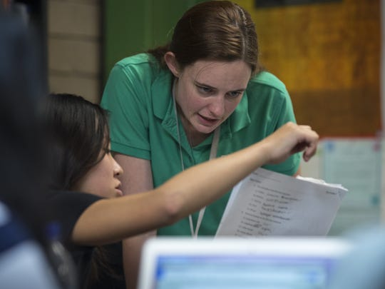 Chemistry teacher Lauren Cooney works with Michelle Koo (left) on April 25, 2017, in their classroom at Basis Scottsdale, 10400 N. 128th St.