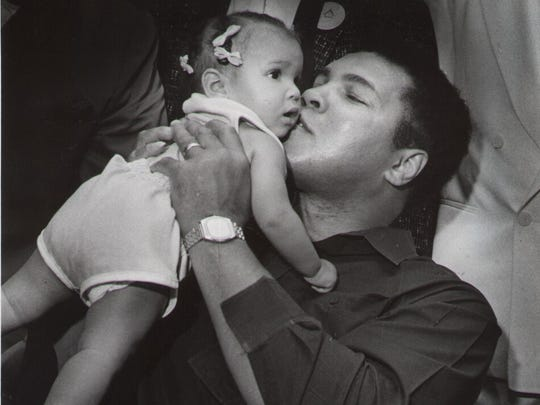 Boxing great Muhammad Ali kisses Camille Brown, 18 months old, during the 1987 Indiana Black Expo luncheon.