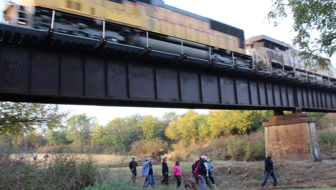 A group of hikers pass under a trestle as a Union Pacific train rushes above them Saturday morning. Several dozen joined Mayor Anthony Williams on the approximately 3-mile hike along Cedar Creek.