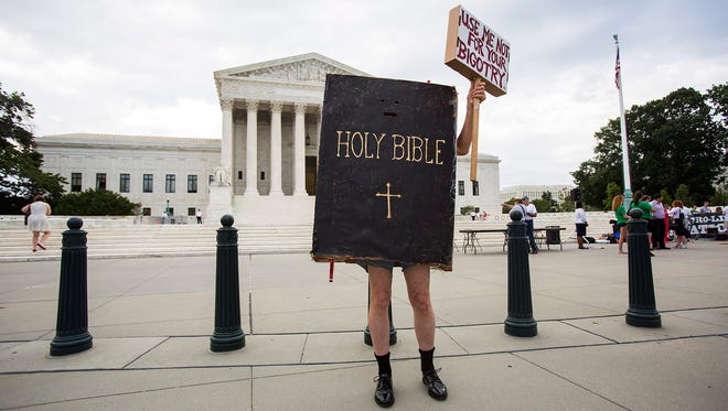epa04291400 A man dressed as the Bible protests outside the US Supreme Court where the nine justices are expected to issue their ruling on the Hobby Lobby case, which challenges the Affordable Care Acts mandate that employee health plans include pregnancy preventive services, in Washington, DC, USA, 30 June 2014. The case was bought by Hobby Lobby, a chain of arts and crafts stores, and is the first major legal challenge to Obamacare in two years.  EPA/JIM LO SCALZO ORG XMIT: JL02