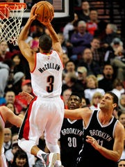 Portland Trail Blazers guard C.J. McCollum (3) hits a shot over Brooklyn Nets center Brook Lopez (11) during the first half of an NBA basketball game in Portland, Ore., Tuesday, Feb. 23, 2016. (AP Photo/Steve Dykes)