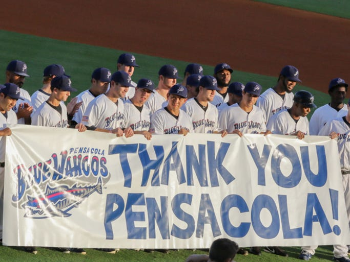 The Pensacola Blue Wahoos hold up a sign thanking fans for their support before the start of the last regular season home game Tuesday night.