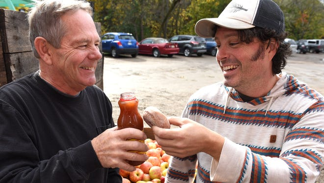 Rob, left, and his son Robbie Nelson toast each other with a jug of cider and a spiced doughnut at their Northville cider mill, Parmenter's, on Oct. 21.