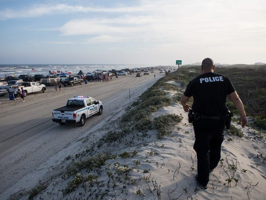Portland Police Officer Gabriel Lopez walks along the dunes in Port Aransas as he pursues a suspect who ran after being stopped for having a glass bottle on the beach during the first day of spring break on Saturday, March 10, 2018.