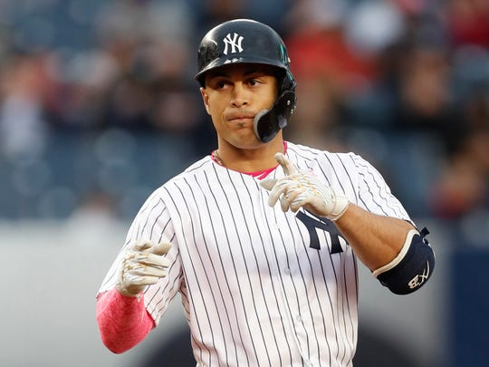 New York Yankees designated hitter Giancarlo Stanton points to the dugout after hitting a seventh-inning double.