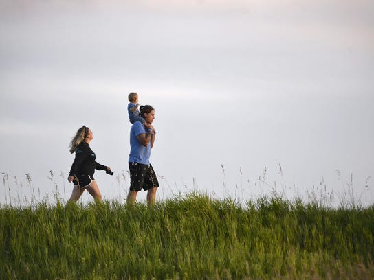A family hikes along the main road in Blue Mounds State