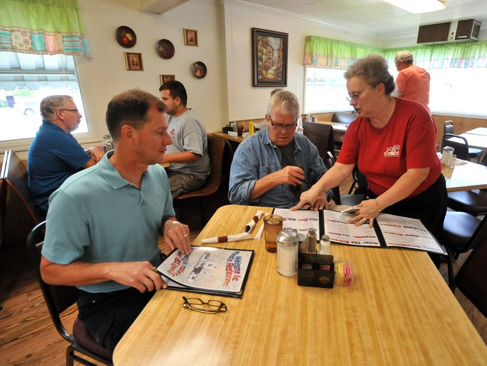 Linda Rowan, left, helps Bruce Westall, center, and Ray Paumier, both from Granville, go over the menu Friday, Aug. 1, 2014, at Roots Restaurant in Lancaster. Rowan has worked at the restaurant for 36 years.