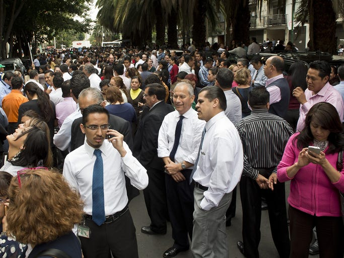 People gather on a street after a strong earthquake on May 8 in Mexico City. A 6.8-magnitude earthquake in Tecpan de Galeana in southern Mexico caused buildings to sway in Mexico City, sending people fleeing into the streets.