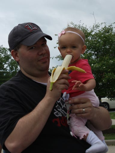 Doug Honour of Burlington feeds a banana to baby Claire, 1, at the Boone County Cooperative Extension Office's Community Activity Fair, celebrating the 100th anniversary of national cooperative extension services.