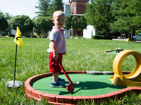 Callum Sutherland, 2, of Knoxville, plays mini golf at the Festival on the Fourth in World's Fair Park Wednesday, July 4, 2018.