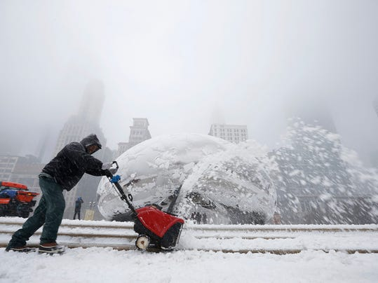 A worker uses a snow blower in front of the Cloud Gate Sculpture during snow in Chicago