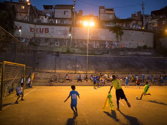 In this Monday, June 2, 2014 photo, children attend a soccer school class on a court in the Mangueira slum of Rio de Janeiro, Brazil. The aspiring soccer stars of Rio de Janeiro's historic Mangueira slum don't have far to look for inspiration. The slum sits on a hill overlooking Brazil's temple to soccer, the fabled Maracana stadium, where legends from Pele to Neymar have played. (AP Photo/Leo Correa)