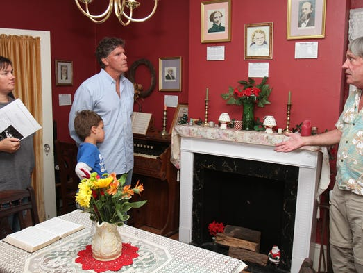 ASB 0811 Asbury Crane   Don Stine, right, president of the Asbury Park Historical Society, gives a tour of the Stephen Crane house on Fourth Avenue in Asbury Park, Sunday, August 10, 2014. Looking on are Svetlana and John Pallone, of Long Branch, and their son John, 6. Mary Frank/Staff Photographer