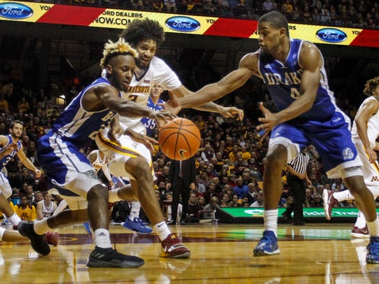 Drake guard Ore Arogundade (23) battles Minnesota forward