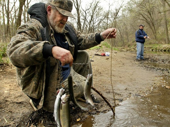 Gerald Barnes, 57, sets a stringer of trout back into the water as his son, Gerald Barnes Jr., 34, angles for more at Backbone State Park in this 2004 photo.