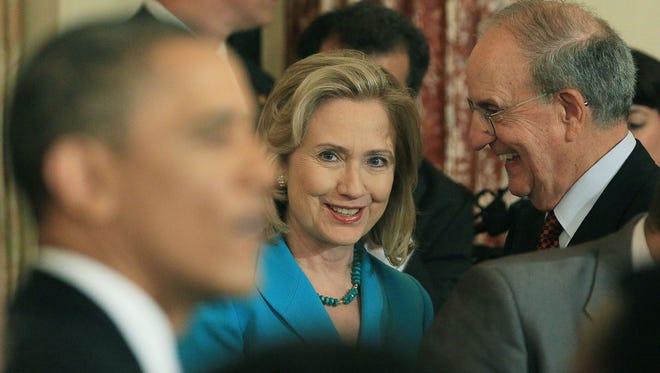 U.S. Secretary of State Hillary Clinton (C) is flanked by George Mitchell (R) while watching U.S. President Barack Obama greet guests after speaking at the State Department on May 19, 2011 in Washington, DC.
