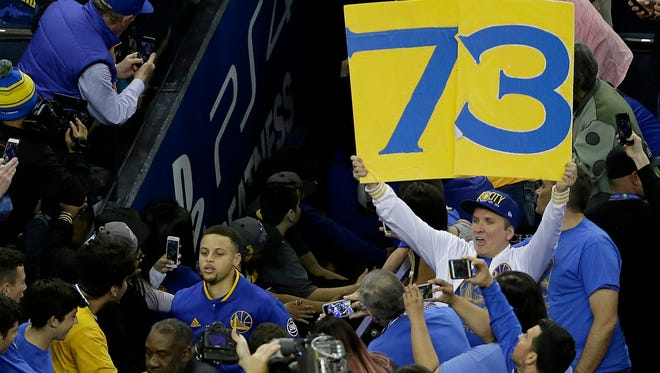 A Golden State Warriors fan holds up a 73 sign as Warriors guard Stephen Curry, bottom left, runs out of the tunnel before an NBA basketball game between the Warriors and the Memphis Grizzlies in Oakland, Calif., Wednesday, April 13, 2016. The Warriors had 72 wins heading into their final regular-season game, the same number of wins as the 1995-1996 Chicago Bulls. (AP Photo/Jeff Chiu)