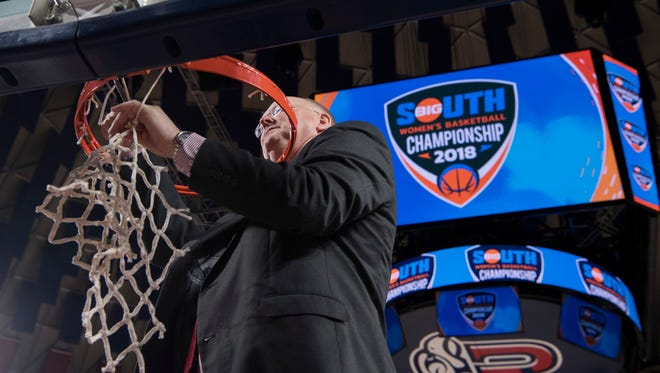 Liberty's head coach Carey Green cuts down the last of the net after defeating UNC Asheville for the Big South Conference  championship in Lynchburg, Va., Sunday, March 11, 2018.
