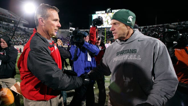 Ohio State football coach Urban Meyer and Michigan State coach Mark Dantonio, right, shake hands following a game Nov. 8, 2014, in East Lansing.