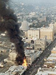 In this April 30, 1992 file photo, a helicopter hovers over smoke and flames rising from a building in Hollywood during the second day of rioting in the city of Los Angeles.