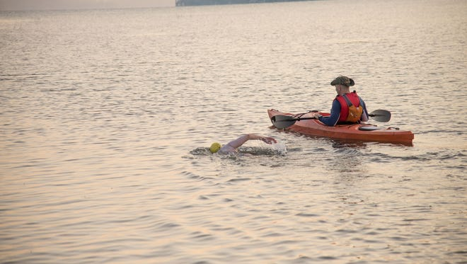 Bridgette Hobart Janeczko swimming the length of Canandaigua Lake, with her husband, Bob, in a kayak, on July 11.