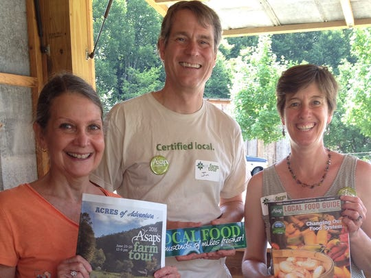At Hickory Nut Gap Farm, ASAP volunteer Meridith Miller, ASAP board member Jim Grode and ASAP volunteer Julie Mayfield display some of the nonprofit's publications.