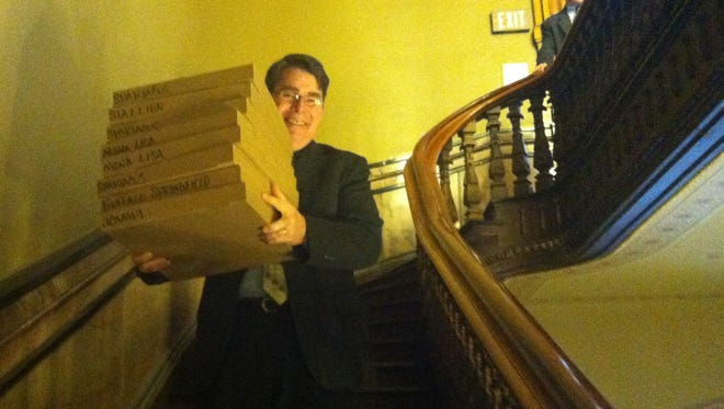 Iowa Senate Majority Leader Michael Gronstal carried a stack of boxes loaded with pizzas in the Iowa Capitol in April 2014 as Democratic legislators took a break as they prepared for an evening floor debate.