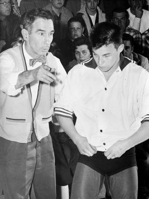 Coleman wrestler Ray Champagne receives instructions from head coach Jim Douglas moments before taking the mat at Coleman High School in 1960.