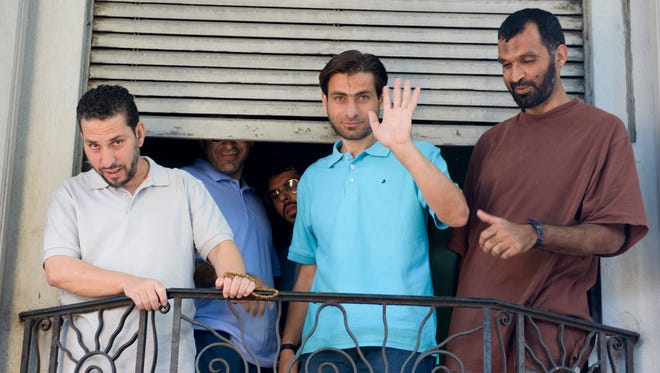 In this Friday, Dec. 12, 2014 photo, Adel bin Muhammad El Ouerghi from Tunisia, stands with fellow, ex-Guantanamo Bay prisoners, on the balcony of the home where they are living in Montevideo, Uruguay. Next to him are Adel bin Muhammad El Ouerghi and Omar Abdelhadi Faraj, from Syria, pictured third from left.
