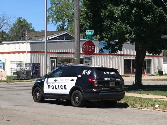 A Wausau police officer sits shortly after noon on