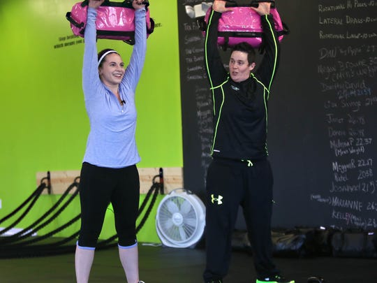 Health reporter Jen Rini lifts 20-lb. bags with Missy Muller, owner of Done Done Fitness, in Middletown.