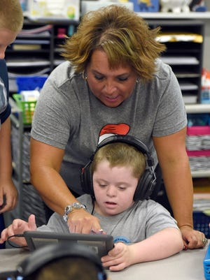 Tekoppel Elementary School teacher Ange Dierks works with Josh Groben as he works on an iPad at the school in Evansville in 2016.