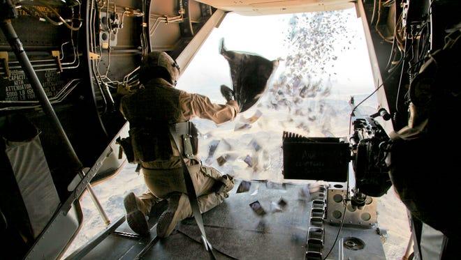 A Marine drops propaganda leaflets in Afghanistan in 2011.