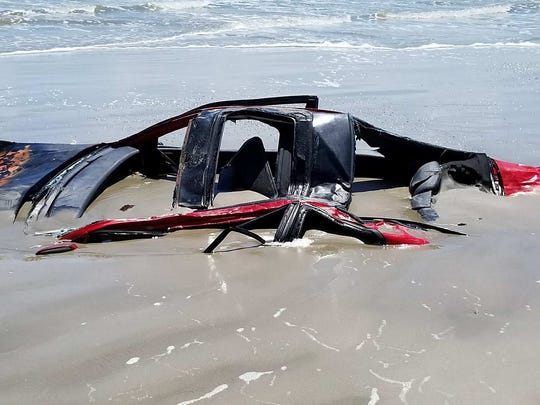 A red Honda Prelude is covered in sand and sustained significant damage after it was left on the beach in Port Aransas before Hurricane Harvey hit the city.