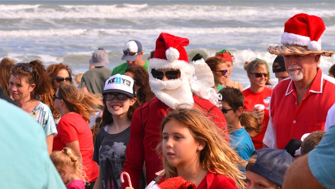 It took Santa a while to make his way up the beach posing for photos and giving kids candy. At 2:00 p.m. Friday after noon, Surfing Santa arrived at Shepard Park in Cocoa Beach, surfing in on eight foot waves with hundreds onshore cheering him on.