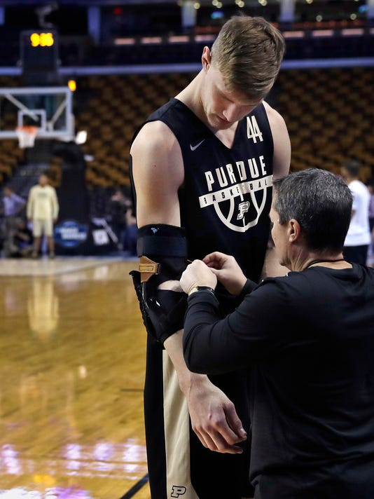 Purdue's Isaac Haas is fitted with an arm brace during practice at the NCAA men's college basketball tournament in Boston, Thursday, March 22, 2018. Purdue faces Texas Tech in a regional semifinal on Friday night. (AP Photo/Charles Krupa)